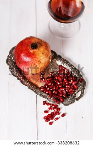 Fresh pomegranate and pomegranate seeds on a vintage silver plate on a white wooden table. Selective focus, shallow DoF - stock photo