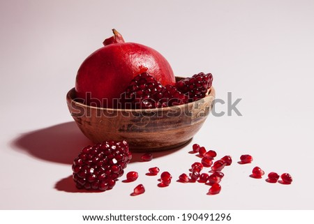 Fresh pomegranate with grains on white background. - stock photo