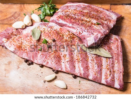 Fresh pork ribs, meat marinated and prepared for roast with garlic parsley allspice - stock photo