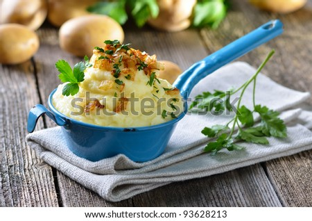Fresh potato puree in an old enamel coated pot - stock photo