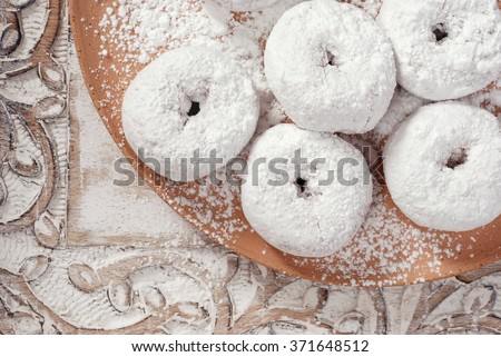 Fresh powdered sugar donuts in rustic setting with hand-thrown pottery plate and distressed wood serving tray.  Closeup from above with soft natural lighting for a vintage feel.