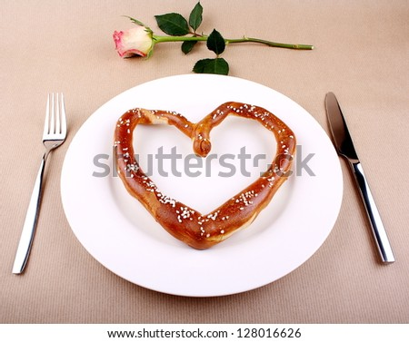 Fresh Pretzel in heart shape with cutlery and Rose