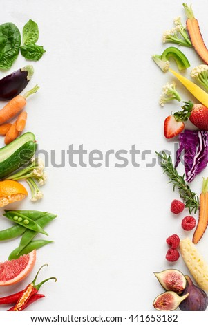 Fresh produce background side border of organic produce colourful fruit and veg, carrot chilli cucumber purple cabbage spinach rosemary herb, poster - stock photo