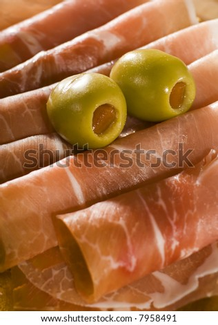 fresh prosciutto with olive fruits close up shoot - stock photo