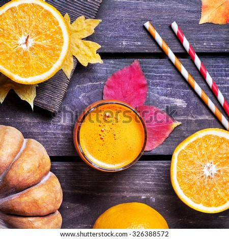 Fresh pumpkin and oranges juice on wooden background in autumn season   - stock photo