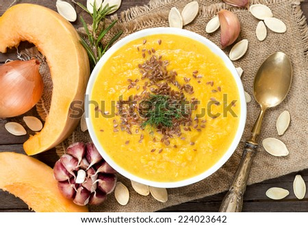 Fresh pumpkin soup with a spoon on a wooden table - stock photo