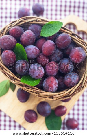 Fresh purple plums in a basket on the wooden board and checkered tablecloth background