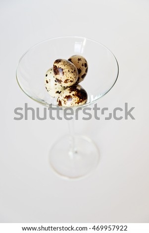 Fresh quail eggs uncooked in a martini glass close up view. Healthy diet and eating conceptual.
