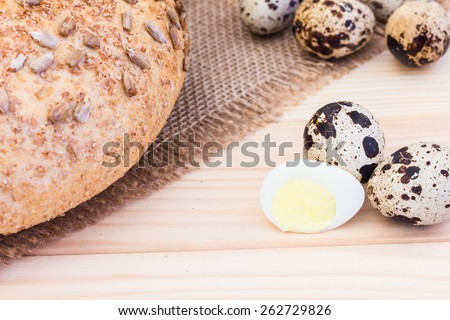 Fresh quail eggs with rye bread on sackcloth - stock photo