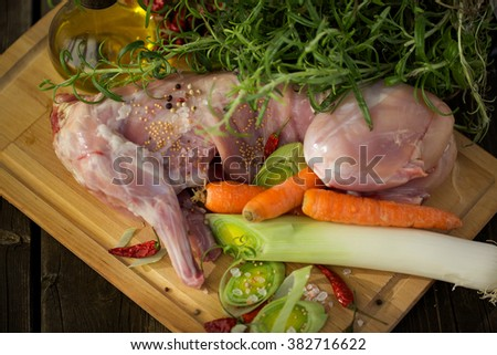 Fresh rabbit meat with vegetables & olive oil for roasting - stock photo