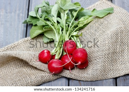 Fresh radishes from ground on old wooden table - stock photo