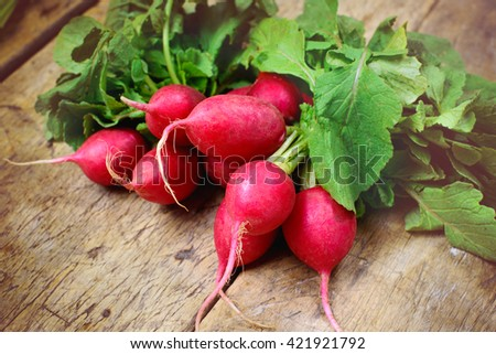 Fresh radishes on old wooden table - stock photo