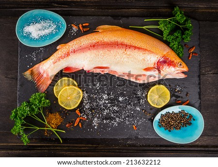 fresh rainbow trout fish with spices on dark wooden table, preparation - stock photo