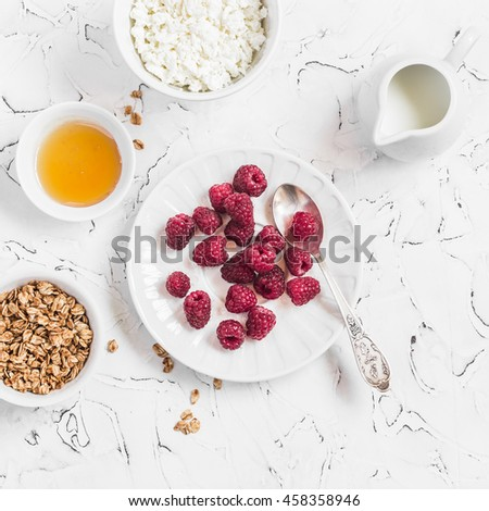 Fresh raspberries, cottage cheese, granola, honey and cream - delicious Breakfast. On a light background, top view - stock photo