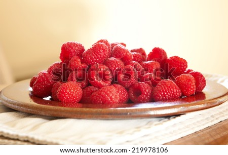 Fresh raspberries on a plate with a shallow DOF - stock photo