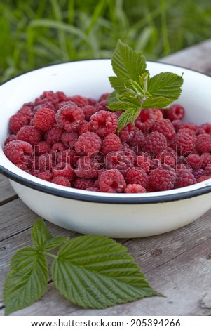 Fresh raspberry in a bowl on wooden table