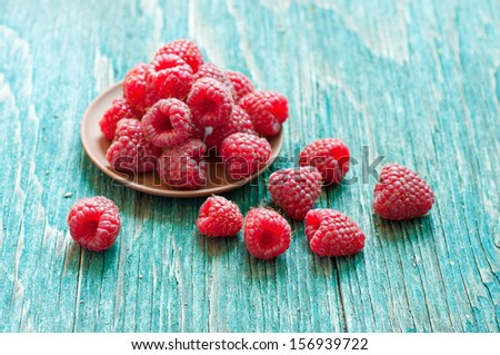 Fresh raspberry in ceramic plate on the blue wooden rustic desk with copy space - stock photo