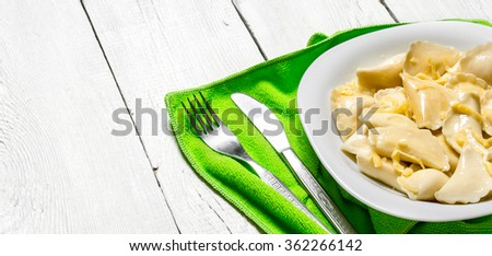 Fresh ravioli with cheese in the plate. On a white wooden background. - stock photo