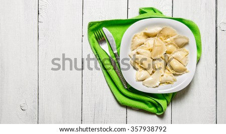 Fresh ravioli with cheese in the plate. On a white wooden background. Free space for text . Top view - stock photo