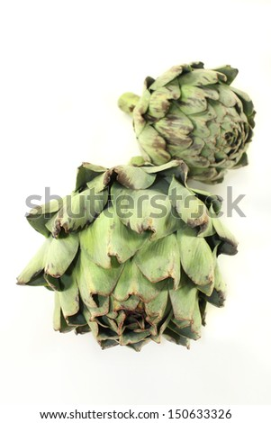 fresh, raw artichoke against a white background - stock photo