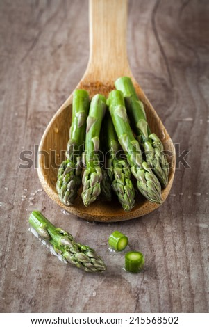 Fresh raw asparagus on wooden spoon - stock photo