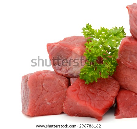 fresh raw beef cubes and parsley on white background