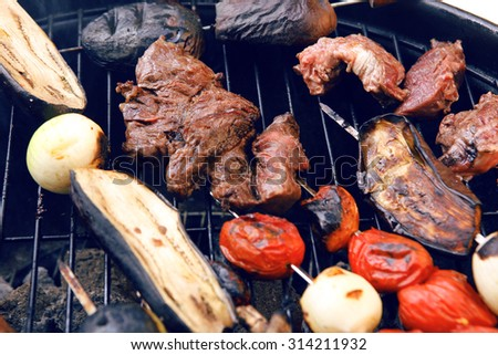 fresh raw beef fillet steak red meat with tomatoes and eggplant on skewers on big round barbecue brazier grid full with ready charcoal selective focus dof - stock photo