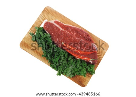 fresh raw beef meat fillet with red hot chili pepper and raw kale leafs on wooden board isolated over white background - stock photo
