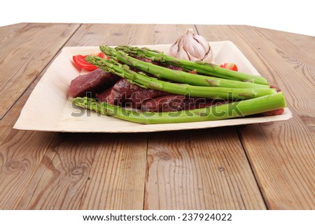fresh raw beef meat steak fillet on wooden plate with asparagus and tomatoes ready to prepare - stock photo