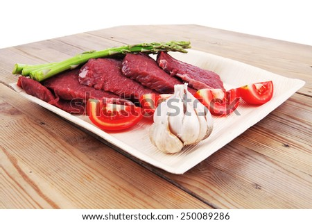 fresh raw beef meat steak fillet on wooden plate with asparagus and tomatoes ready to prepare