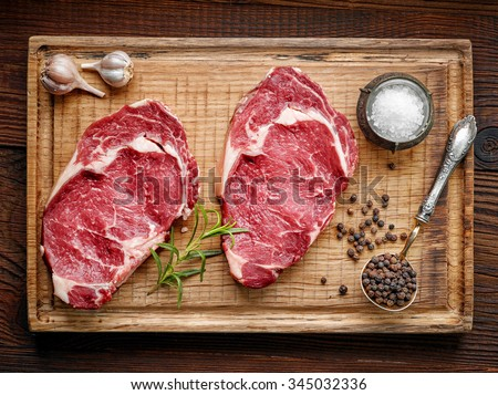 fresh raw beef steak on wooden cutting board, top view - stock photo