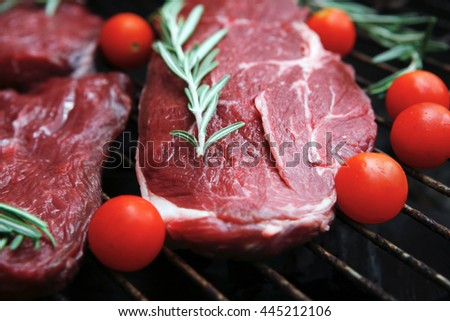 fresh raw beef steak with cherry tomatoes rosemary twig and red pepper bell on black bbq grill ready to prepare