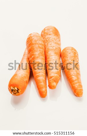 Fresh raw carrots on a white background.
