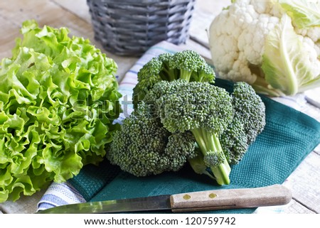 Fresh raw cauliflower, broccoli and lettuce on towel on wooden background. Selective focus - stock photo