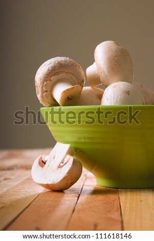 fresh raw champignon mushrooms in the green bowl on the wooden table - stock photo