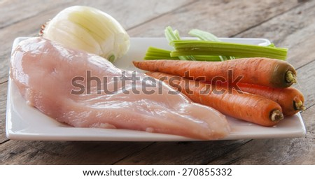Fresh raw chicken fillet and vegetables prepared for cooking - stock photo