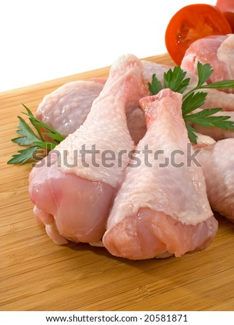 Fresh raw chicken legs on wooden board
