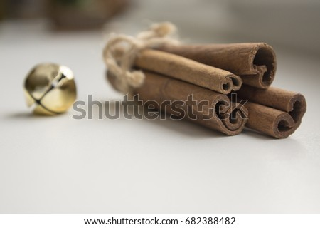 Fresh raw cinnamon sticks on wooden table tied with natural twine and jingle bells