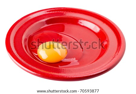 Fresh raw egg served on red plate isolated - stock photo