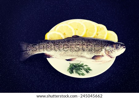 Fresh raw fish lying on a plate with lemon's slices. - stock photo