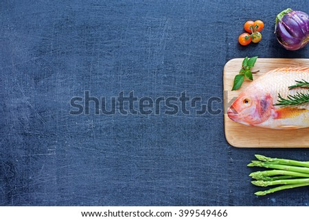 Fresh raw fish (Nile tilapia) with herbs and vegetables (eggplant, cherry tomato and asparagus). Dark background. Space for text. - stock photo