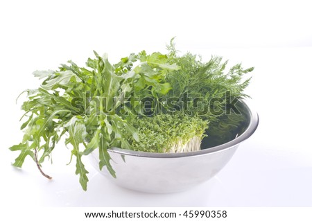 Fresh raw herbs in a metal bowl over white background