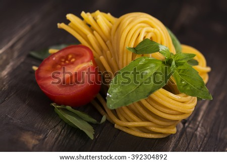 Fresh raw homemade pasta over grunge wooden table. Selective focus - stock photo