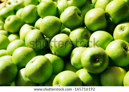 fresh raw lot of green apples on counter - stock photo