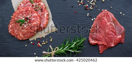 Fresh raw meat and burger cutlets from the farmers market on a black grunge table. Selective focus, flat lay - stock photo