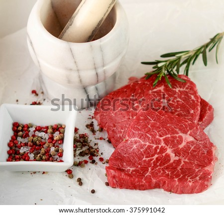 Fresh raw meat and spices. Marbled beef, rosemary and pepper on the table. The ingredients to prepare a delicious dinner. Selective focus - stock photo