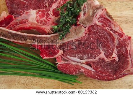 fresh raw meat : fresh red beef ribs with green sprouts on wooden board isolated over white background - stock photo