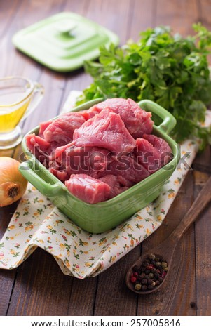 Fresh raw meat in bowl on table with whole pepper, oil, herbs. Selective focus. - stock photo