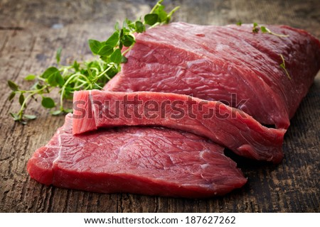 fresh raw meat on old wooden table - stock photo