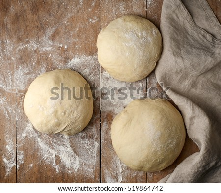fresh raw pizza dough on wooden rustic table, top view